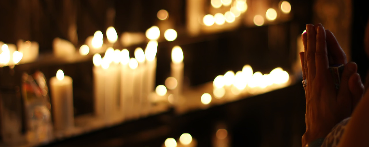 close-up-photograph-of-person-praying-in-front-lined-candles-1024900